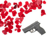 Gun between the rose petas — Stock Photo
