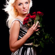 Pensive blonde woman with bunch of roses — Stock Photo