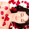 Portrait of beautiful brunette woman lying in rose petals — Stock Photo