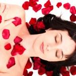 Portrait of beautiful brunette woman lying in rose petals — Stock Photo #6123145