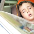 Litle boy sleeps in safe chair in car — Stock Photo