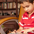 Stock Photo: Little boy play smartphone game in leather chair