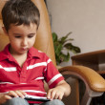 mały chłopiec gry smartphone w skórzanym fotelu — Zdjęcie stockowe