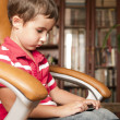 Little boy play smartphone game in leather chair — Stock Photo #6640985