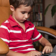 Little boy play smartphone game in leather chair — Stock Photo #6640987