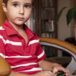 Little boy play smartphone game in leather chair — Stock fotografie #6640991