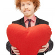 Handsome man with red heart-shaped pillow - Stok fotoraf