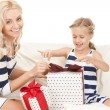Mother and little girl with gifts - Stock Photo