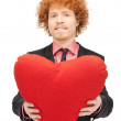 Handsome man with red heart-shaped pillow — Stock Photo #5395320