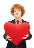 Handsome man with red heart-shaped pillow — Stock Photo