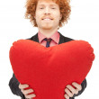 Handsome man with red heart-shaped pillow — Stock Photo #5418240