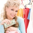 Stock Photo: Lovely womwith piggy bank and money