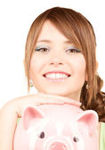 Lovely teenage girl with piggy bank — Foto de Stock