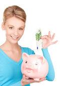 Mooie vrouw met piggy bank en geld — Stockfoto