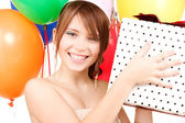 Party girl with balloons and gift box — Stock Photo