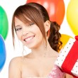 Party girl with balloons and gift box - Stock Photo