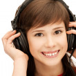 Stock Photo: Happy teenage girl in big headphones