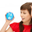 Teenage girl holding alarm clock — Stockfoto