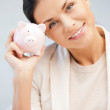 Lovely woman with piggy bank - 图库照片