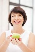 Lovely housewife with green apple — Zdjęcie stockowe