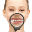 Teenage girl with magnifying glass showing teeth — Stock Photo