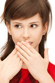 Teenage girl with palms over mouth — Stock Photo