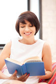 Happy and smiling woman with book — Stock Photo