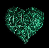 Broken green glass heart isolated on black background — Stock Photo