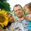 Mom, dad and baby in sunflower field — Stock Photo