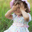 Little girl playing peek-a-boo - Stock Photo