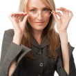Young woman putting on glasses — Stock Photo