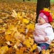 Laughing toddler and falling leaves — Stock Photo