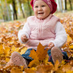 Smiley girl on yellow leaves — Stock Photo #5759088