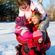 Parents with daughters playing in snow — Stock Photo