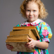 Stock Photo: Preschool girl carrying books