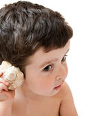 Little boy listening to seashell sounds, isolated — Stock Photo