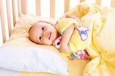 Smiling baby in crib — Stock Photo