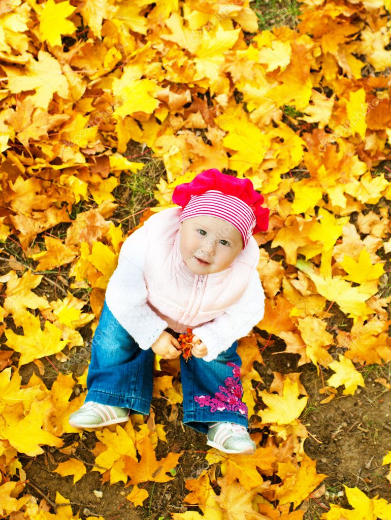 Baby sitting in autumn leaves and looking up — Lizenzfreies Foto #5759098