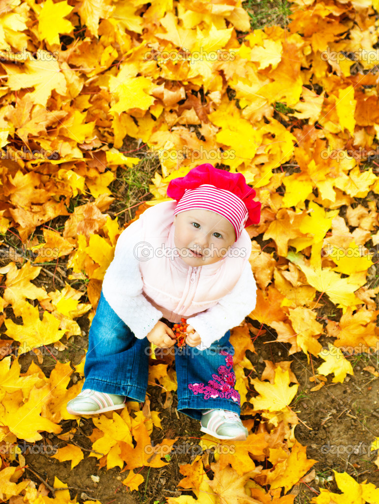 Baby sitting in autumn leaves and looking up  Stok fotoraf #5759098
