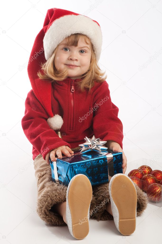 Little girl in Santa hat holding present box — Stock Photo #5759123