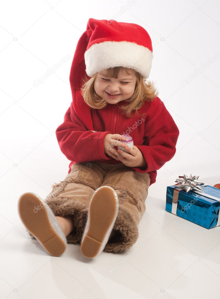 Little girl in Santa red hat playing — Stock Photo #5759126