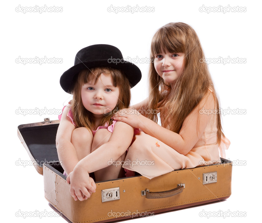 Two girls sitting in the old-styled shabby suitcase — Stock Photo #5759442