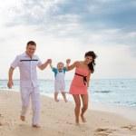 Family running along the beach — Stock Photo