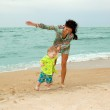 Baby and his mother walking on the beach — Stock Photo #5760325