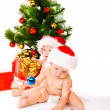 Babies beside Christmas tree — Stock Photo #5761109