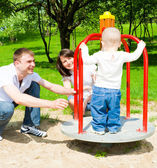 Parents rotating merrygoround — Stock Photo