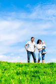 Happy young family on green grass over sky — Stock Photo