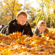 Daddy and doughter on autumn leaves — Stock Photo