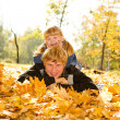 Daddy and daughter on autumn leaves — Stock Photo