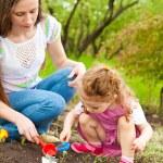 Daughter helping mom in garden — Stock Photo